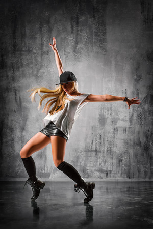 modern dance: young beautiful dancer posing on studio background