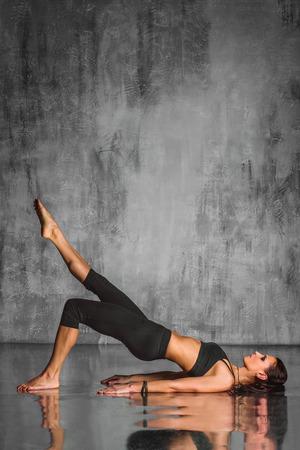 jonge mooie yoga poseren op een grijze achtergrond studio Stockfoto