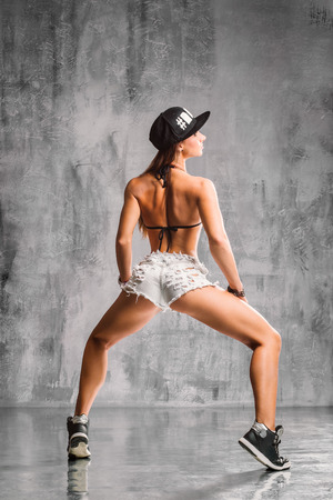 young beautiful booty dancer posing on studio background Stock Photo