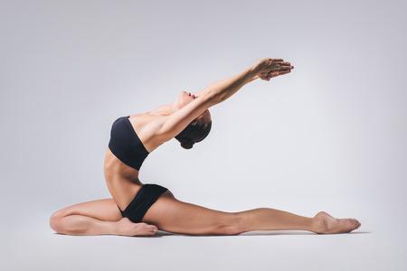 nude yoga: young beautiful yoga posing on a gray studio background