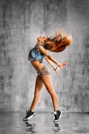 dancing pose: young beautiful dancer posing on studio background