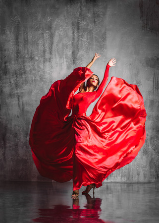 dancer in red dress posing on studio background Stock Photo