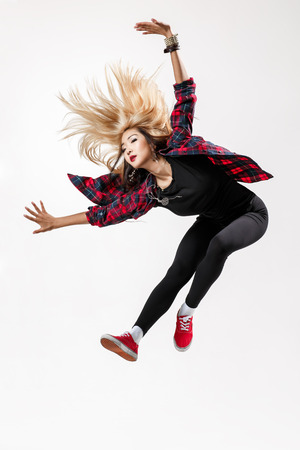 young beautiful dancer jumping on a studio background photo