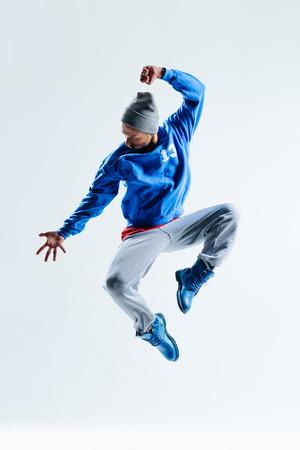 スタジオの背景上でジャンプ若い美しいダンサー