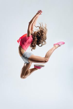 danza moderna: joven y bella bailarina que salta en un fondo del estudio