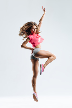 young beautiful dancer jumping on a studio background Stock Photo
