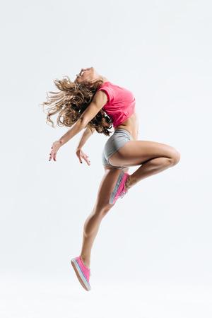 스튜디오 배경에 점프 젊은 아름다운 댄서