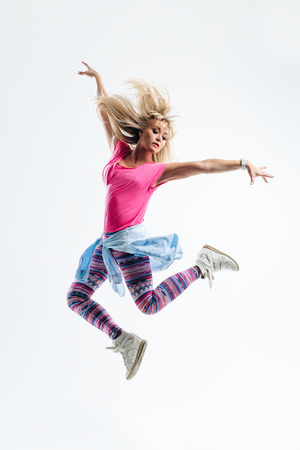 dancer: young beautiful dancer jumping on a studio background Stock Photo