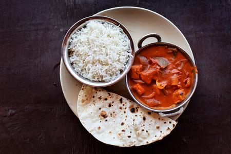 tandoori chicken: Chicken tikka masala served with rice on the table