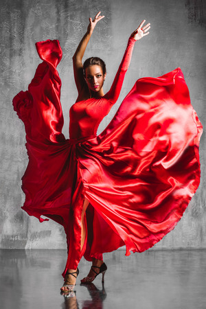 beautiful flamenco dancer posing on a studio background Standard-Bild