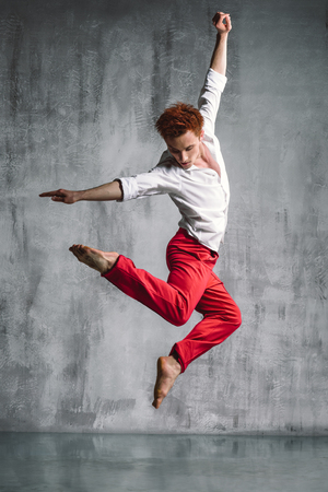 male ballet dancer: young beautiful modern style dancer posing on a studio background