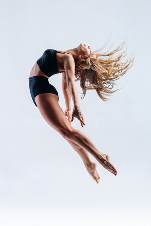 contemporary: young beautiful modern style dancer posing on a studio background