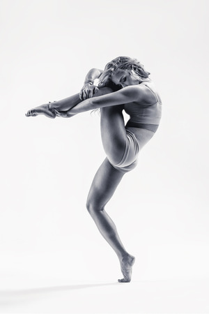 fitness dance: young beautiful modern style dancer posing on a studio background