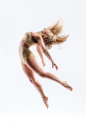 leap: young beautiful modern style dancer posing on a studio background