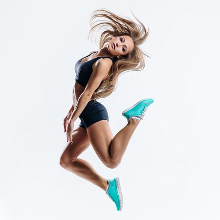 glamour woman elegant: beautiful fitness female posing on studio background
