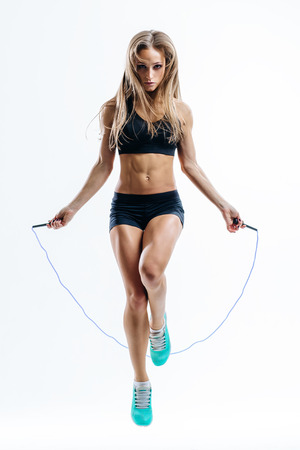 skipping: beautiful fitness female posing on studio background