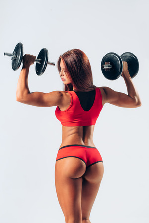 sexual activities: beautiful fitness female posing on studio background with barbells Stock Photo