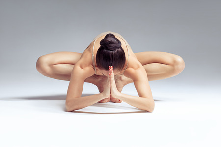 prana: young beautiful yoga female posing on a studio background
