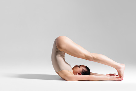 kundalini: young beautiful yoga female posing on a studio background