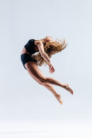 スタジオの背景にポーズをとって若い美しいモダン ダンサー 写真素材