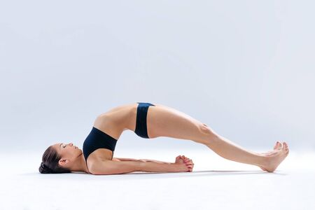young beautiful yoga female posing on a studio background photo