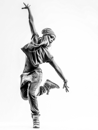 an action: Young beautiful dancer jumping in studio