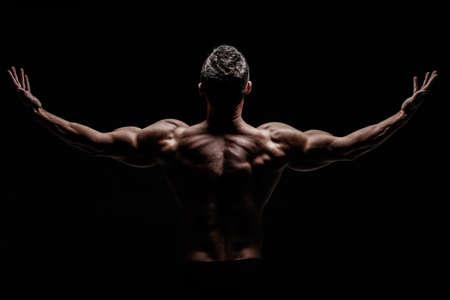 nudo maschile: Young muscular bodybuilder posing over black background. Archivio Fotografico