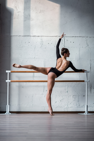 barre: Young beautiful ballerina posing in studio Stock Photo