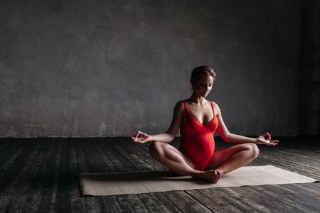 Jonge mooie zwangere yoga poseren in de studio Stockfoto - 86528344