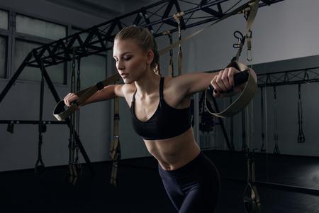 스포티 한 여자 TRX 운동 체육관에서 하 고