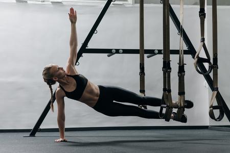 Sportieve vrouw die TRX-oefeningen in de gymnastiek doet