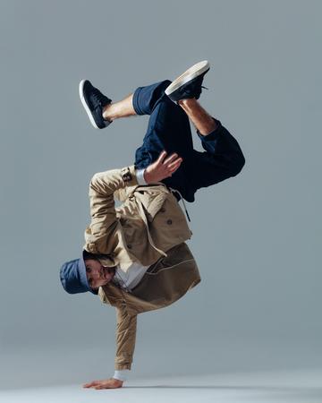 Junger schöner männlicher Tänzer, der im Studio aufwirft