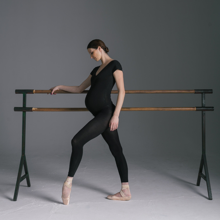 Young beautiful pregnant ballerina is posing in studio