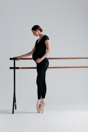 Young beautiful pregnant ballerina is posing in studio
