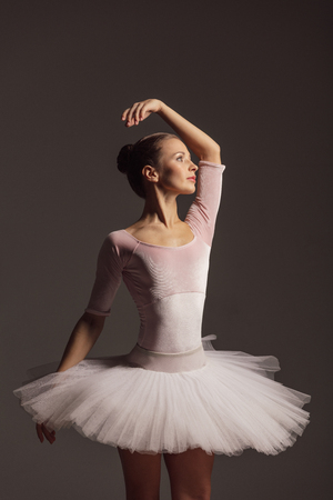 Young beautiful ballerina is posing in studio