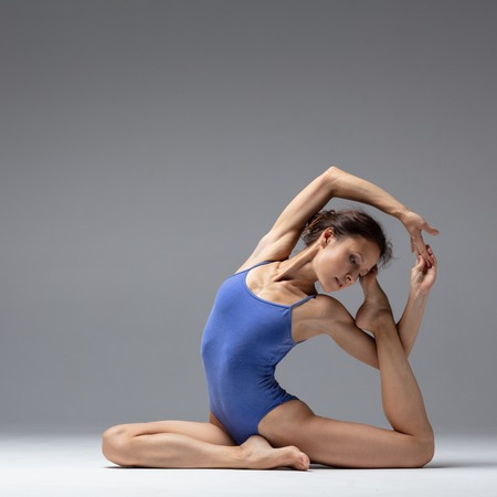 Young beautiful yoga woman is posing in studio Stock Photo