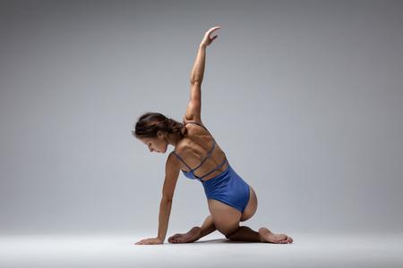Young beautiful yoga woman is posing in studio