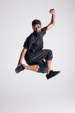 Hip hop dancer moving and jumping in photostudio Фото со стока