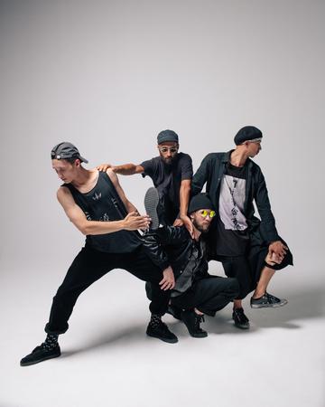 Bailarines de hip hop moviéndose y saltando en estudio fotográfico. Foto de archivo