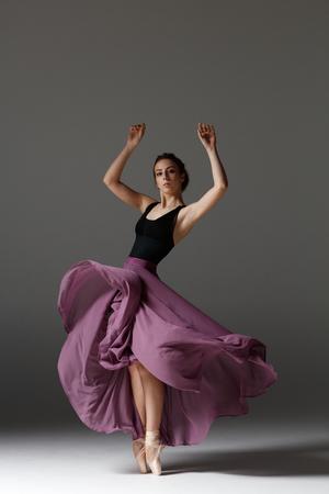 Joven bailarina hermosa está posando en estudio