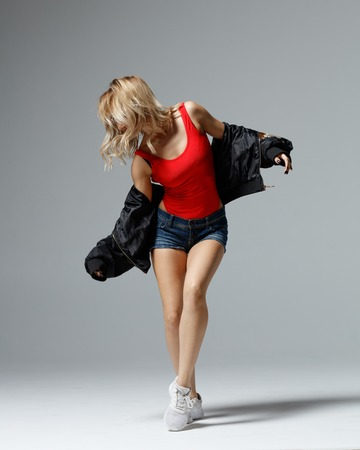 Hip hop dancer moving and jumping in studio