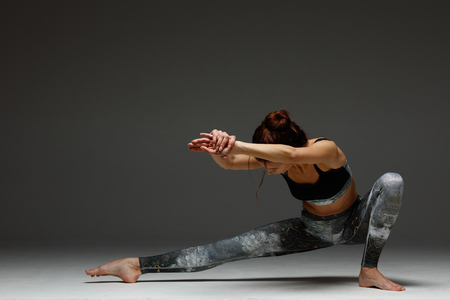 Young beautiful yoga instructor is posing in studio.