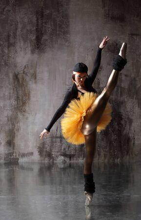 Young beautiful ballerina is posing in studio