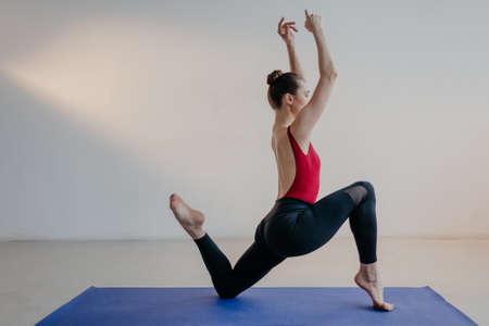 Young beautiful yoga woman is posing in studio. Reklamní fotografie