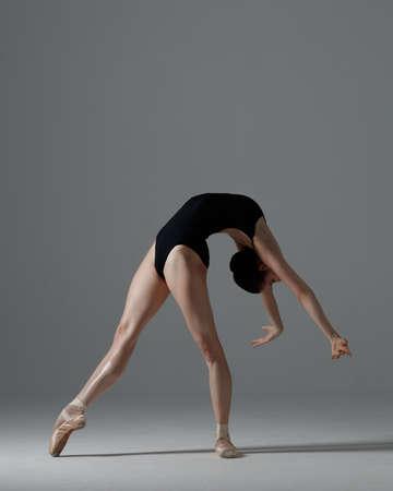 Young beautiful ballet dancer is posing in studio Imagens