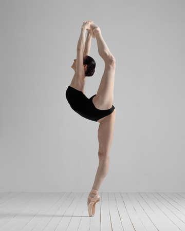 Young beautiful skinny ballerina is posing in studio
