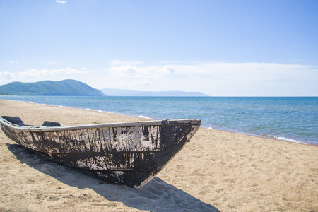 Old wooden boat on the beach in a bright, Sunny, summer day. Stock Photo
