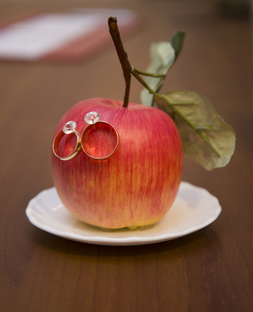 Wedding rings hanging on a red Apple. Wedding. Ceremony.