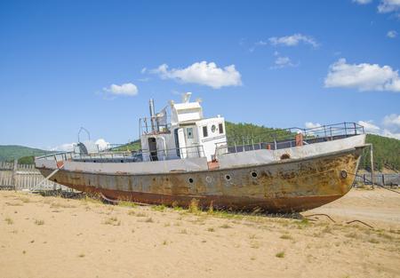 Old broken, rusty ship on the coast. The ship graveyard.