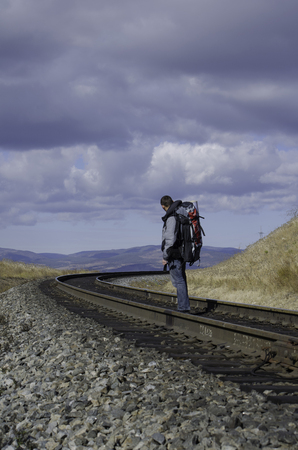 The traveler stands by the railroad tracks and waiting for trains.